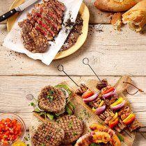 Hamburgers en barbecue spiezen op een houten tafel