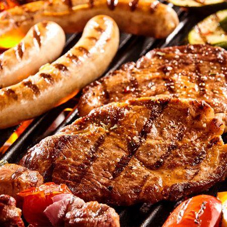 Worstjes en twee biefstukjes op een barbecue