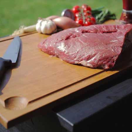Groot stuk vlees op plank met mes ernaast